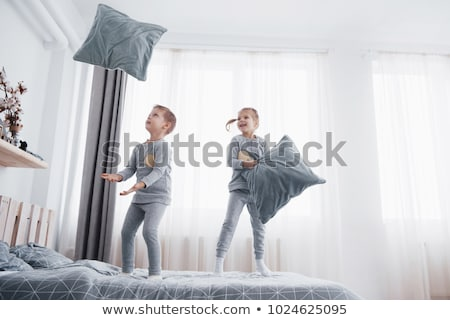 girl and boy jumping on bed stock photo © bluering