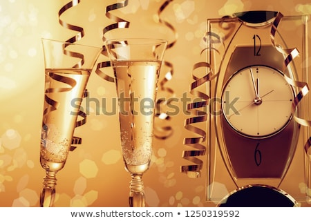 Stock photo: Champagne glasses against holiday lights and clock close at midn