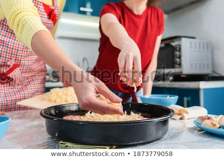 Couple Sprinkling Cheese On Pizza Stock photo © AndreyPopov