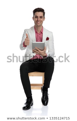 seated  man holding tablet pad computer and makes the ok Stock photo © feedough