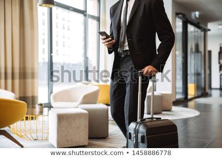 Portrait of handsome businesslike man wearing suit, standing nea Stock photo © deandrobot
