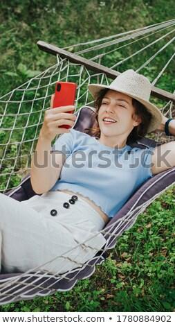 женщину гамак смотрят Новости мобильного телефона расслабляющая Сток-фото © AndreyPopov