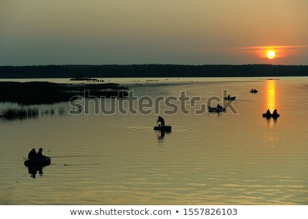 Man in Inflatable Boat with Oar, Pond or Lake Stock photo © robuart