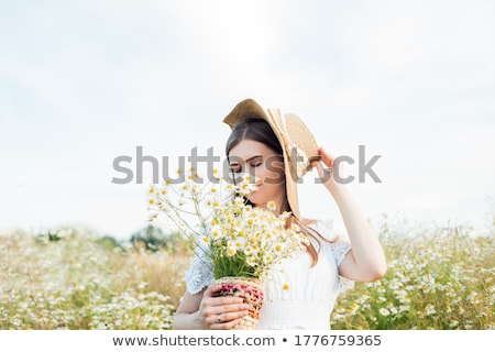 beautiful woman enjoying daisy in a field stock photo © lopolo