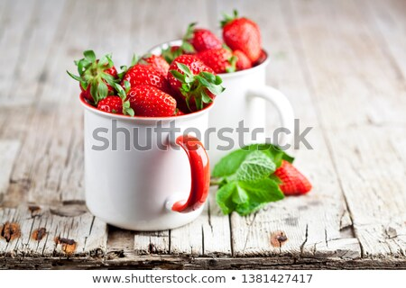 Organic red strawberries in two white ceramic cups on rustic woo Stock photo © marylooo