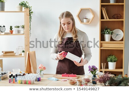 Blonde female in apron putting handmade soap bar into paper packet Stock photo © pressmaster