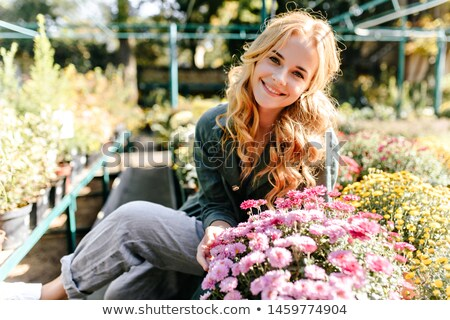 A woman smiles in the Botanical garden against a background of thick green trees Stock photo © ElenaBatkova