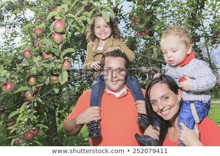 A happy family of four attractive caucasian catch apple on a fie Stock photo © Lopolo