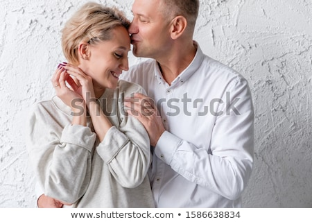 Portrait of young family couple embrace each other and hold their favourite pet, smile gladfully at  Stock photo © vkstudio