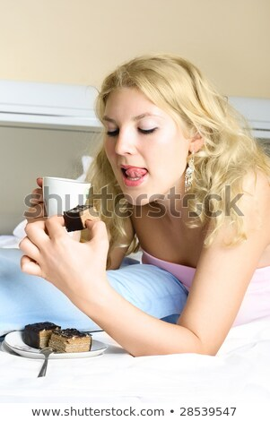 Stock photo: beautiful blonde woman licking chocolate from her lips