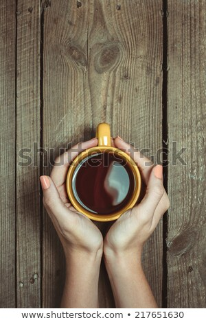 Stock photo: young woman holds in hands of cups on saucer in shop