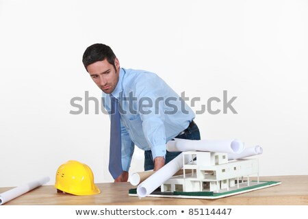 Annoyed architect piling rolled-up drawings on a model Stock photo © photography33