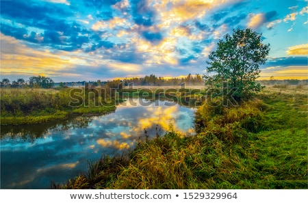Coucher du soleil rivière arbres bleu Photo stock © bobhackett