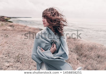 young woman standing in sand dunes wrapped in blanket stock photo © monkey_business