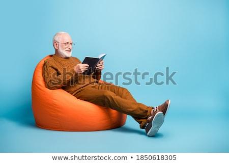 Uomo pullover occhiali seduta libro adulto Foto d'archivio © feelphotoart