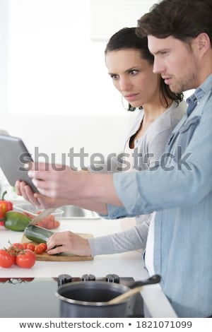 Young woman Following Recipe On Digital Tablet Stock photo © Witthaya