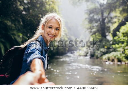 Happy young woman leading man Stock photo © deandrobot
