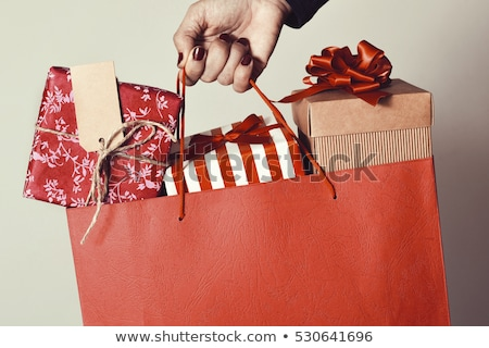 Stock photo: Happy woman holding shopping bags and gift boxes.