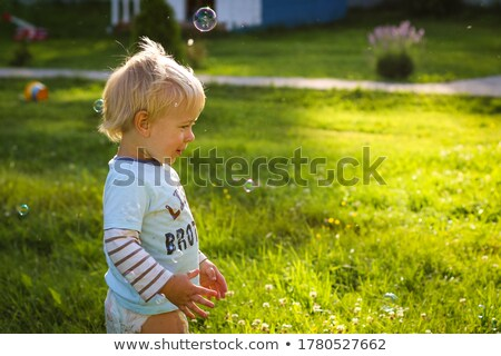 Couple in sun catching bubbles Stock photo © IS2