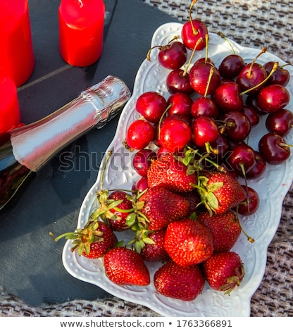 Bottle of rose champagne, glasses with fresh strawberries and heart shaped gift Stock photo © dash