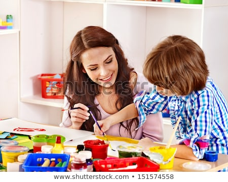 Mother and daughter painting together at home with paintbrushes and watercolors Stock photo © Lopolo