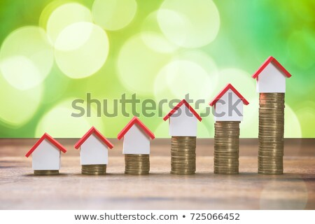 Stock photo: Stack Of Coins And House Model On Desk