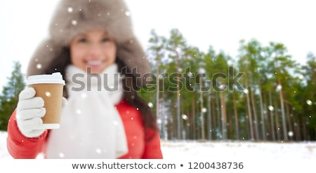 woman in fur hat with coffee over winter forest Stock photo © dolgachov