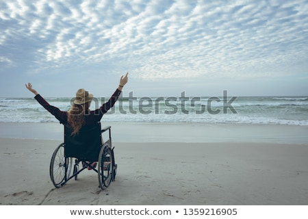 Rear view of disabled woman with arms stretched out sitting on wheelchair at beach in the sunshine Stock photo © wavebreak_media