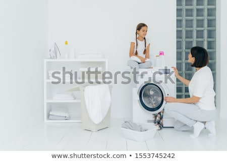 Busy brunette woman loads washing machine with dirty clothes, her little daughter helps, stands near Stock photo © vkstudio