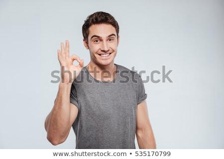 Souriant jeune homme signe de la main geste Photo stock © dolgachov