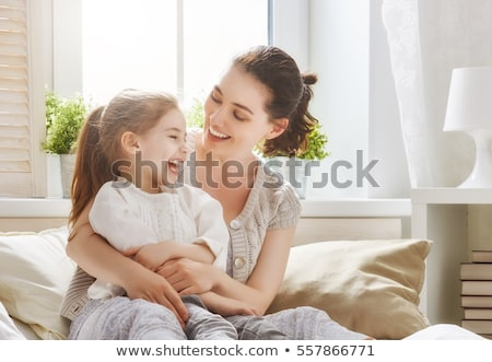 Lovely family of young mother and her small daughter embrace friendly, have good relationships, dres Stock photo © vkstudio
