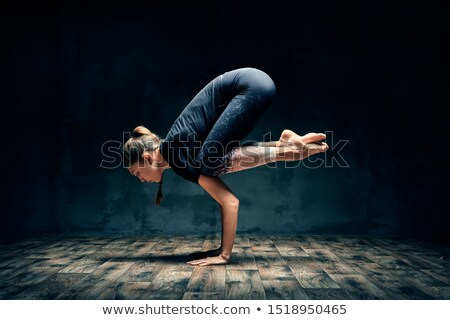 Young woman practicing yoga doing forearm stand crane pose asana in dark room Stock photo © GVS