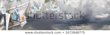 100 Dollar Bills with Medical Face Mask Falling From Stormy Clou Stock photo © feverpitch