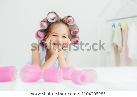 Delighted little girl against white background lying on a bed Stock photo © wavebreak_media