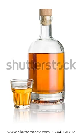 Bottle and beveled shot glass filled with amber liquid Stock photo © Zerbor