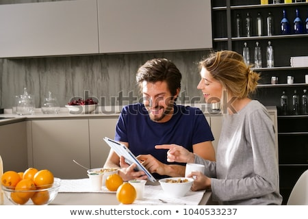 cheerful young couple having breakfast and using tablet stock photo © deandrobot