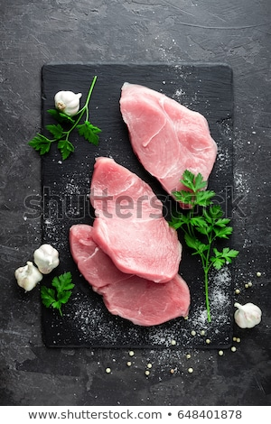 Raw meat, turkey steaks on black background, top view Stock photo © yelenayemchuk