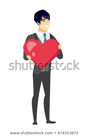 Asian groom holding a big red heart. Stock photo © RAStudio