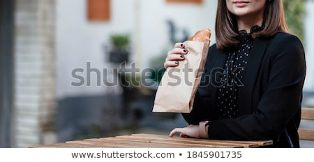Cheerful young lady sitting indoors with croissant drinking juice Stock photo © deandrobot