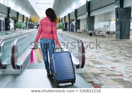 woman with shopping bags on escalator stock photo © is2