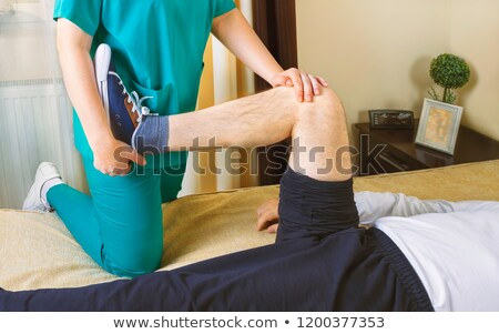 physiotherapist doing exercises for leg recovery to immobilized stock photo © manaemedia