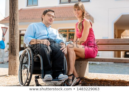 man in wheelchair and woman eating nibbles spending time stock photo © kzenon
