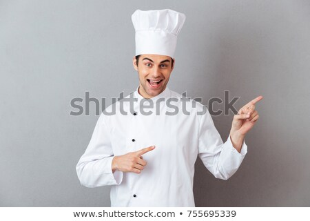 Chef man isolated over white wall background looking camera make thumbs up. Stock photo © deandrobot