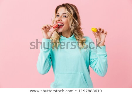 Photo of pretty woman in basic clothing holding two macaron bisc Stock photo © deandrobot