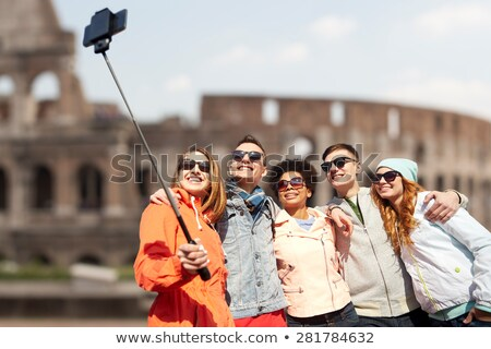 friends taking selfie by monopod over coliseum stock photo © dolgachov