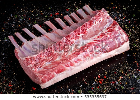 Fresh raw pieces of pork ribs on chopping board and vintage meat hatchet, fork and knife on wooden b Stock photo © DenisMArt