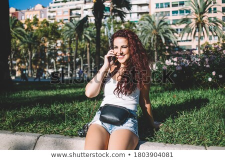 Portrait of caucasian curly woman 20s smiling and talking on mob Stock photo © deandrobot