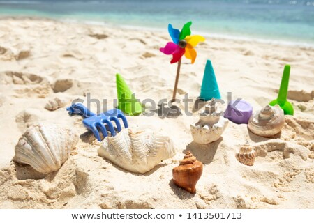 Stock photo: Pinwheel, Plastic Toys And Seashells On Sand At Beach
