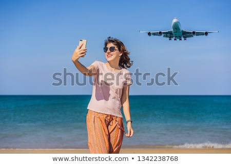 Woman makes a selfie on the beach watching the landing planes. Traveling on an airplane concept. Tex Stock photo © galitskaya