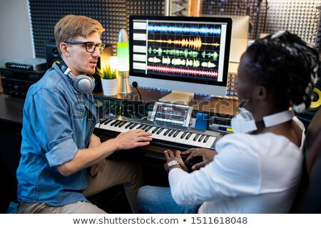 Multi-ethnic musicians in casualwear sitting by workplace in recording studio Stock photo © pressmaster